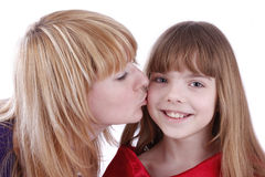 Mother is kissing her happy daughter. Royalty Free Stock Photos