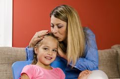 Mother kissing her little girl in the head royalty free stock image