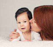 Mother kissing her little newborn baby royalty free stock image
