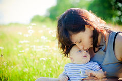 Mother Kissing Her Little Son. Young mother kissing her little son on a field of camomile Stock Image