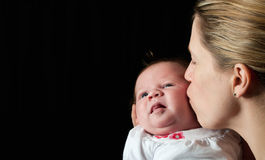 Mother kissing her new born baby Stock Photos