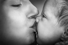 Mother kissing her newborn baby. Close-up black and white portrait Royalty Free Stock Photography