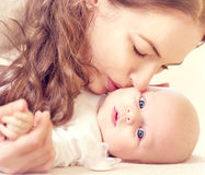 Mother kissing her newborn baby stock photo