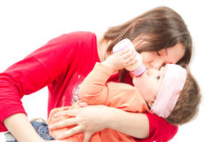 Mother kissing her smiling baby girl on the cheeks Royalty Free Stock Photography