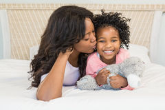 Mother kissing her smiling daughter on bed Stock Photography