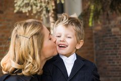 Mother kissing her son. Mother kissing her 4 years old son outdoors Royalty Free Stock Image
