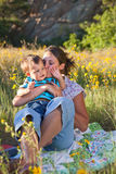 Mother kissing her son. Sitting on a blanket in middle of wildflowers Stock Images