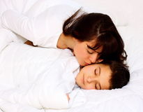Mother kissing her son. While he sleep covered with white blanked Royalty Free Stock Images