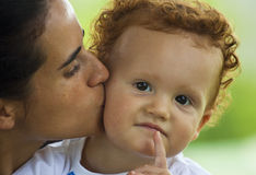 Mother kissing her son. A mother giving her young son a kiss on his cheek Stock Image