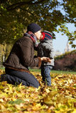 Mother kissing her son. At autumn park Royalty Free Stock Photography