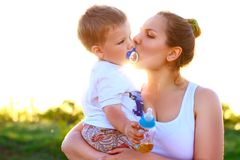 Mother kissing her son on a background of green trees Stock Photos