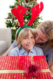 Mother kissing her son at Christmas time. In the living-room Stock Photography