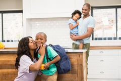 Mother kissing her son going to school Stock Photos