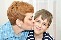 Mother kissing her son. Happy mother kissing her adorable young son Stock Images