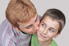 Mother kissing her son. Happy mother kissing her adorable young son royalty free stock images