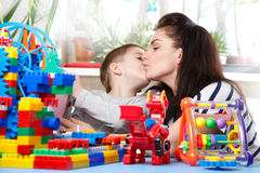 Mother kissing her son  in home interior. Mother kissing her son sitting at a table with toys in home interior Stock Photo