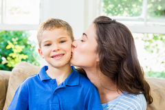 Mother kissing her son in living room. Affectionate mother kissing her son in living room Stock Photos