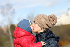 Mother kissing her son. At the park in autumn Royalty Free Stock Photo