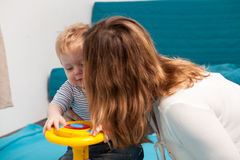 Mother kissing her son while he is playing. Happy childhood and parenting Royalty Free Stock Images