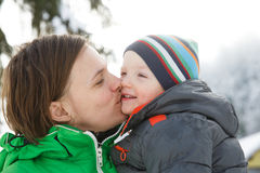 Mother kissing her son in a snowy winter landscape. Bonding, having fun, smiling, talking and enjoying family time. Mothers day, family values, parents love Royalty Free Stock Photo