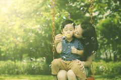 Mother kissing her son on the swing. Picture of young women kissing her son while playing with soap bubbles and sitting on the swing. Shot in the park Royalty Free Stock Photography