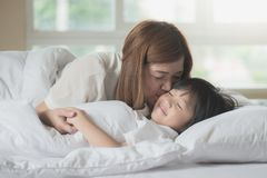 Mother  kissing her son on white bed. Asian mother  kissing her son on white bed Royalty Free Stock Images