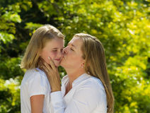 Mother kissing her young daughter on side of face Royalty Free Stock Photography