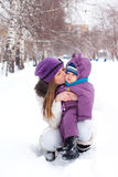 Mother kissing and holding a baby, winter Stock Photos