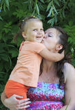 Mother kissing little daughter. Stock Photo