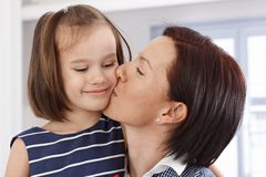 Mother kissing little daughter's face Royalty Free Stock Photos