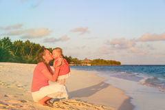 Mother kissing little daughter at sunset beach Royalty Free Stock Photography