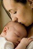 Mother kissing newborn baby Royalty Free Stock Image