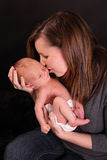 Mother kissing newborn baby. Half body portrait of mother kissing newborn baby boy; black background stock photos
