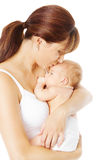 Mother kissing newborn baby holding in hand, white Royalty Free Stock Images