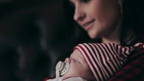 Mother kissing newborn baby near Christmas tree closeup stock footage