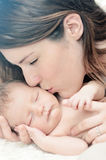Mother kissing newborn baby. A mother kissing and showing affection for her newborn baby stock images