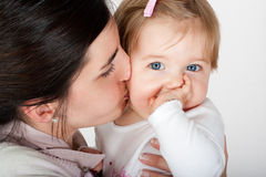 Mother kissing and playing with her baby Stock Image