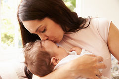 Mother Kissing Sleeping Baby Boy At Home Stock Photography