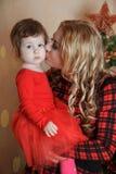 Mother kissing small daughter at Christmas Royalty Free Stock Photos