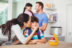 Mother kissing smiling son wearing schoolbag Royalty Free Stock Photos