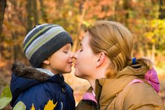 Mother kissing son in autumn scenery Stock Photo