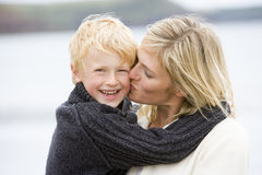 Mother kissing son at beach smiling Stock Photo