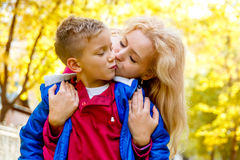 Mother kissing sun among autumn Royalty Free Stock Photos