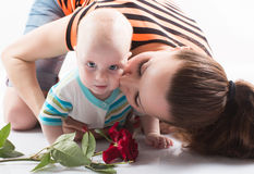 Mother kissing sweet baby boy. Beautiful mother kissing sweet baby boy stock images