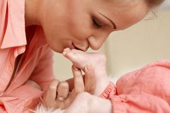 Mother kissing sweet baby foot Royalty Free Stock Photography