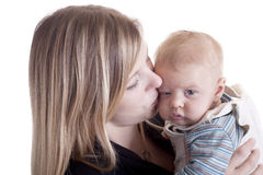 Mother kissing tired baby Royalty Free Stock Image