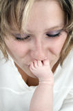 Mother kissing the tootsie of her baby Royalty Free Stock Image