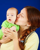 Mother kissing young baby Stock Photos