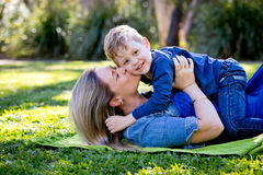 Mother kissing young son on cheek whilst playing together on rug Stock Photos