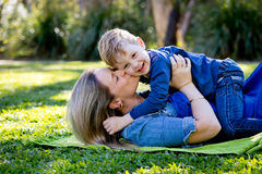 Mother kissing young son on cheek whilst playing together on rug Royalty Free Stock Image